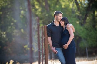 A couple expecting their first child embraces in a field at Fausel Ranch in Placerville, California.