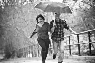 A newly engaged couple runs through the rain in Sacramento, California