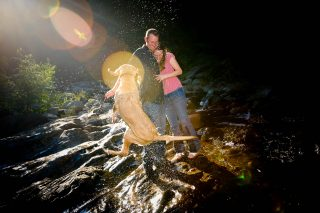 A newly engaged couple plays with their dog down by the river in Pollock Pines, CA