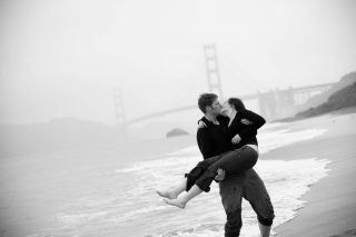 An engagement kiss on the beach by the Golden Gate Bridge in San Francisco, California.