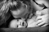 Mother kissing her smiling baby in Sacramento, California.