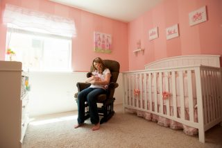 A new mother rocks her baby to sleep in a cute pink nursery in Sacramento, California.