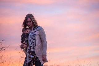 A mom carries her newborn daughter in a baby carrier at sunset at Sly Park Lake in Pollock Pines, California.