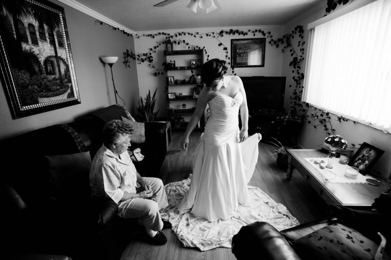 A grandmother helps her grand daughter get in her wedding dress on her wedding day.