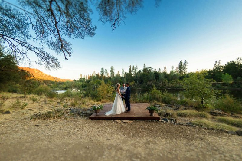 A couple exchanges their vows in the late afternoon light along the riverside in Coloma, California.