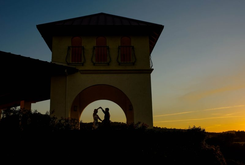 A silhouette of a couple dancing in the sunset during their wedding reception at David Girard Vineyards in Placerville, California.