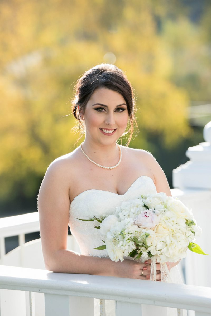 A natural image of a bride holding her bouquet of flowers as she poses for a portrait at Sequoia Mansion in Placerville, California.