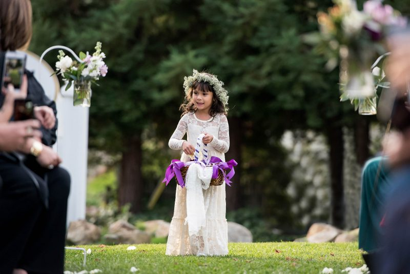 A flower girl makes her way down the aisle at Sequoia Mansion in Placerville, California.
