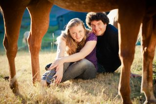 A farm couple peers through the legs of their horse during their Fausel Ranch engagement session.