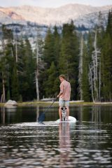 Young man and his dog on stand up paddleboard on a mountain lake