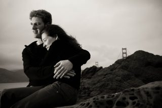 A couple hugs by the Golden Gate Bridge in San Francisco, California.