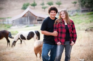 A couple poses for a photo at their Fausel Ranch farm engagement session in Placerville, California.