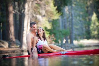 A couple enjoys a paddle boarding engagement session in Lake Tahoe, California.