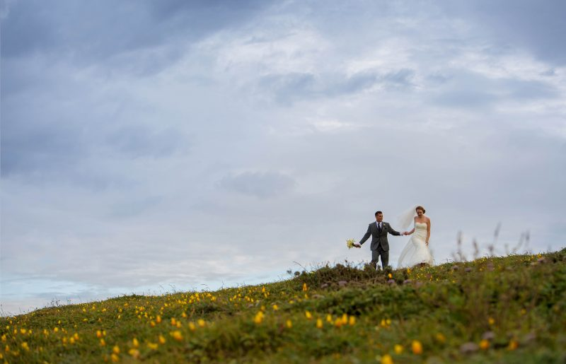 A bride and groom walking on a hillside of yellow flowers in Bodega Bay overlooking the Pacific Ocean.