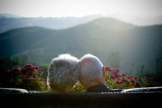Long-married couple sits on bench overlooking mountains