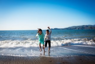 Brother and sister laughing playing in the water on the beach